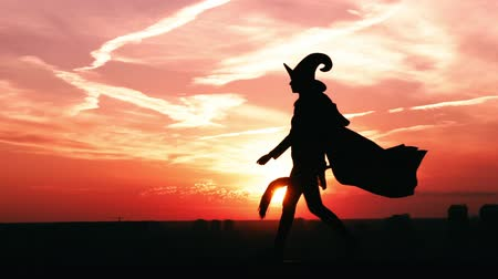 hag : witch in hat and fluttering cloak with besom walks sunrise view on the city slow motion halloween