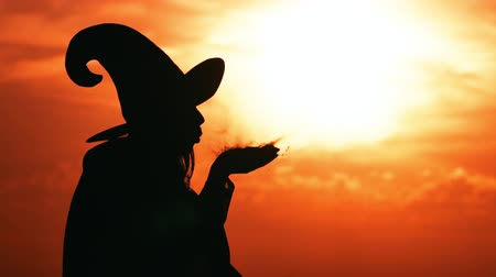 hag : silhouette side view woman witch costume blowing on magic powder outdoors in city view on sky at sunrise halloween concept