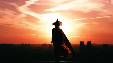 hag : silhouette back view woman witch costume sprinkles magic potion outdoors city view sky at sunrise halloween concept