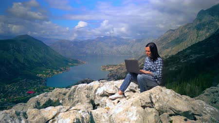 climber rock : woman traveller sitting on the rock typing on computer view of the mountainous area with blue water houses in the valley surrounded trees