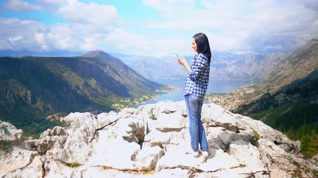 tırmanıcı : woman traveller standing on the rock scrolls feed social media or sharing photo view of the mountainous area with blue water houses in the valley surrounded trees Stok Video