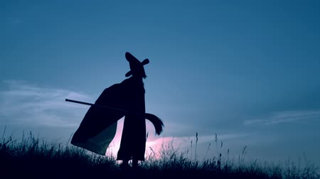 hallows : woman in a witch costume and broom have fun slow motion view on evening blue sky halloween holiday