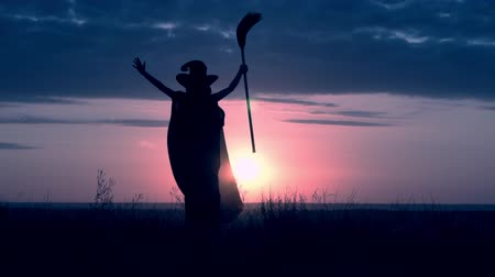 besom : woman in halloween costume sorceress holding besom celebrating the beginning of the day of all saints standing on the hill sky with yellow sun