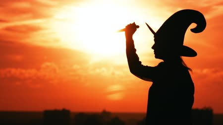 hag : silhouette woman hag in hat holding knife posing outdoors in city view on sky at sunrise halloween concept