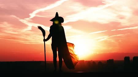 witch hat : silhouette woman in hat and holding broom posing outdoors in city view on sky at sunrise halloween concept