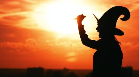 hag : silhouette woman hag in hat holding knife screams outdoors in city view on sky at sunrise halloween concept Stock Footage