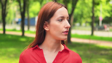 caráter : happy caucasian female in red shirt standing on the street turns head to the camera smiling nature summer background Stock Footage