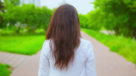 joyfulness : young woman wearing casual white hoodie walks on the street with nature background green trees surrounded road