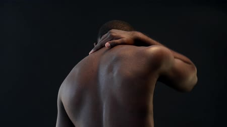 atlet : African-american man rubbing his neck with hand because of pain in the neck on black background Stok Video