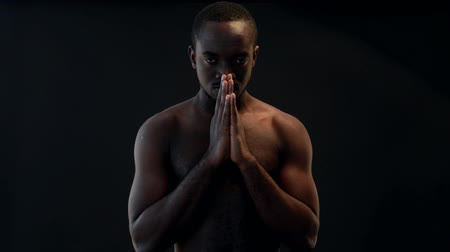 dua eden : African-american man praying on black background