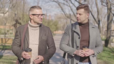 tea bag : Two handsome adult men with cups of coffee talking while walking in the park Stock Footage