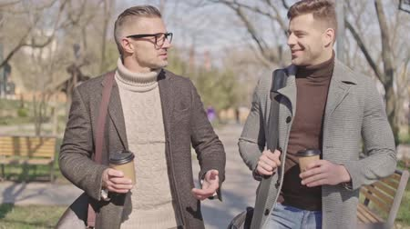 tea bag : Two stylish adult men with cups of coffee speaking while walking in the park