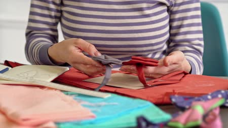 решить : Attractive young woman seamstress comparing two bow-ties for making new sketch at her workplace Стоковые видеозаписи