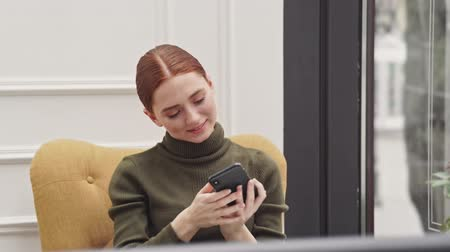 gestos : Smiling young redhead lady taking selfie photo on smartphone sitting in the cafe