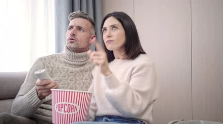 pipoca : Happy lovely couple watching tv together and eating popcorn at home