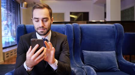 fauteuil : Smiling bearded business man using smartphone while sitting on armchair in cafe Stockvideo
