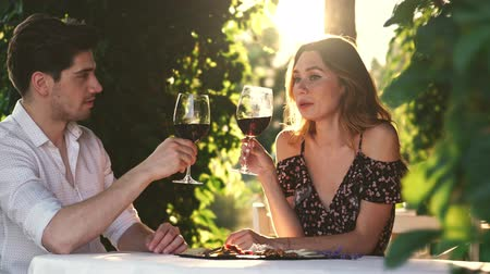 keyifli : Closeup of young loving couple sitting outdoors drinking wine talking with each other Stok Video