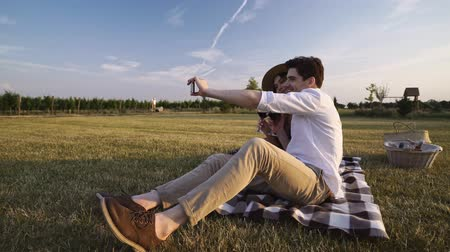 plezant : Young happy loving couple sitting outdoors in the field drinking wine talking with each other take a selfie with mobile phone Stockvideo