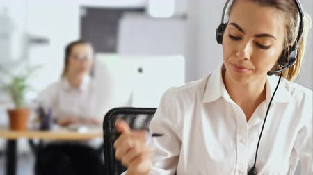 callcenter : Young beautiful concentrated business woman working in office using pc computer and headphones with mic