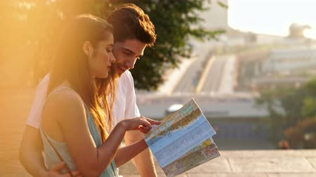 navigovat : Young happy loving couple walking outdoors at the street holding map talking Dostupné videozáznamy