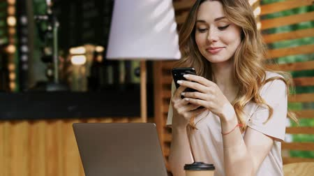 studenti : Close up view of Smiling brunette woman in casual clothes sitting by the table with laptop computer while using smartphone at cafe outdoors