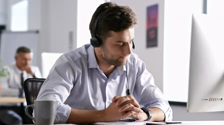 escritórios : Serious concentrated brunette man in shirt talking in headphones with subscriber while working in call center Stock Footage