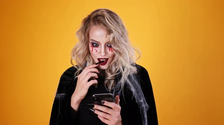 magie : Surprised woman wizard wearing black costume and halloween makeup using smartphone over orange background