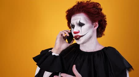 szörnyszülött : Happy mystical clown with halloween makeup talking by smartphone over orange background