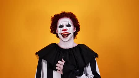 урод : Laughing mystical clown with halloween makeup looking at the camera over orange background