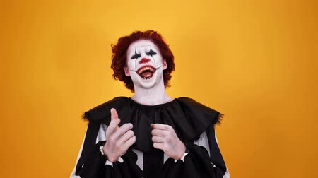 урод : Laughing clown with halloween makeup looking at the camera over orange background
