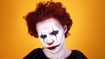 урод : Close up view of Upset clown with halloween makeup looking around over orange background Стоковые видеозаписи
