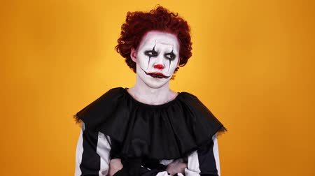 урод : Upset clown with halloween makeup looking around with crossed arms over orange background