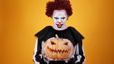 урод : Angry clown with halloween makeup holding pumpkin and looking at the camera over orange background
