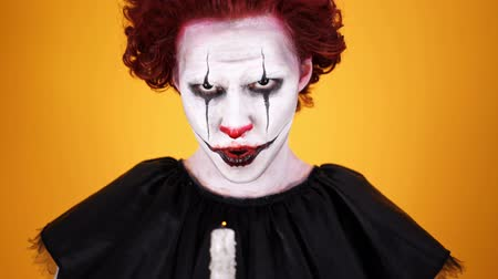 scary clown : Close up view of Angry clown with halloween makeup holding candle and looking at the camera over orange background Stock Footage