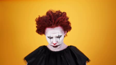 szörnyszülött : Close up view of Angry clown with halloween makeup holding pumpkin and looking at the camera over orange background Stock mozgókép
