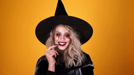 witch hat : Joyful mystery woman wizard wearing black costume and halloween makeup looking at the camera over orange background