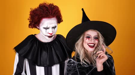 tréfacsináló : Cheerful witch woman and clown man wearing black costume and halloween makeup having fun together over orange background