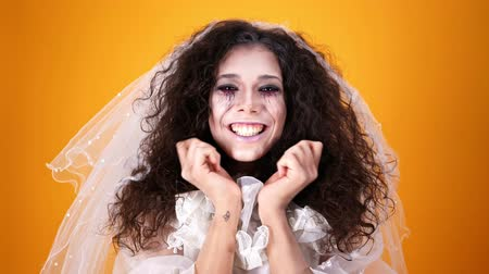 kötülük : Crazy dead bride on halloween wearing wedding dress and makeup laughing and looking at the camera over orange background