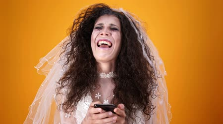 feiticeiro : Upset crying dead bride on halloween wearing wedding dress and makeup using smartphone and looking at the camera over orange background