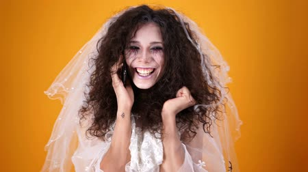 zauberer : Happy dead bride on halloween wearing wedding dress and makeup talking by smartphone over orange background Videos