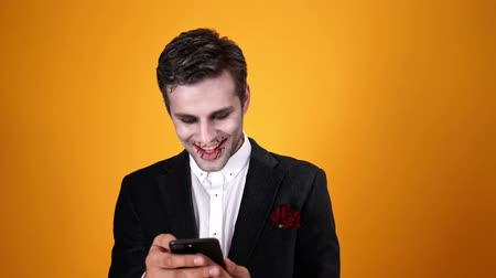 feiticeiro : Surprised happy dead bridegroom in halloween makeup using smartphone over orange background Stock Footage