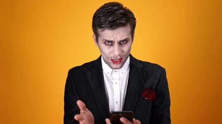 feiticeiro : Shocked dead bridegroom in halloween makeup using smartphone over orange background Stock Footage