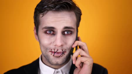 zombi : Confused dead bridegroom in halloween makeup with sutured mouth trying to talk by smartphone over orange background Stok Video