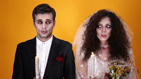 each other : Mystery dead married couple in halloween makeup posing together with candles over orange background Stock Footage