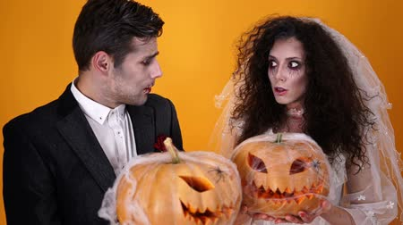 each other : Mystery dead married couple in halloween makeup posing together with pumpkins over orange background