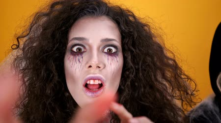 scary clown : Group of creepy characters in halloween costumes and makeup having fun together over orange background Stock Footage
