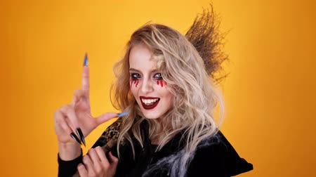 feiticeiro : Cheerful woman wizard wearing black costume and halloween makeup posing with broom and looking at the camera over orange background