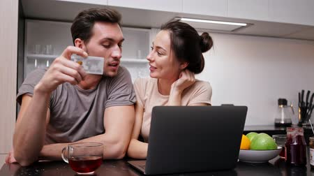 video making : Happy loving couple using laptop computer and making purchases while sitting together at kitchen Stock Footage