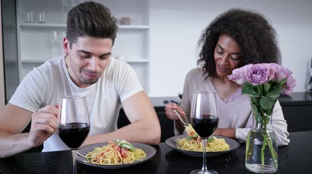 şarap kadehi : Pleased loving multiethnic couple drinking wine and eating while sitting on kitchen