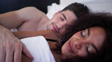 adormecido : Close up view of Pleased loving multiethnic couple sleeping together on bed Vídeos